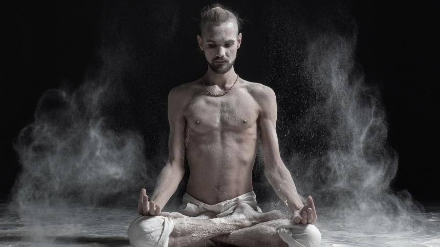 Sporty serene young man meditating sitting in cross-legged yoga lotus pose, Padmasana with palms in mudra. Dust flying in air. aghori concept